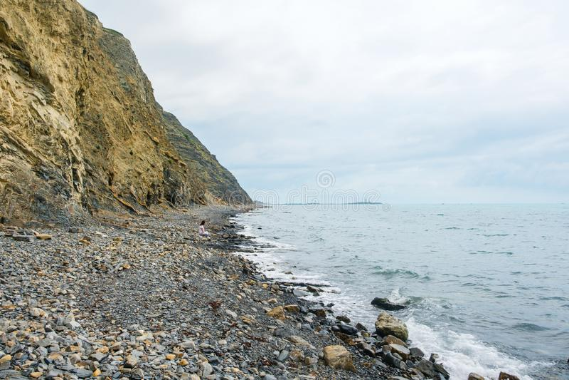 Moça só que senta-se na costa entre a rocha e o mar fotos de stock royalty free