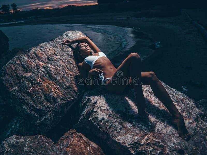 A moça sensual, 'sexy' com um corpo escultural magro sedutor em um roupa de banho é de encontro e de levantamento nas rochas na n imagem de stock