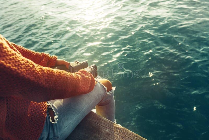 A moça senta-se em Pier With Binoculars In Hand e aprecia-se a ideia da natureza, vista traseira Escuteiro Wanderlust Concept imagem de stock