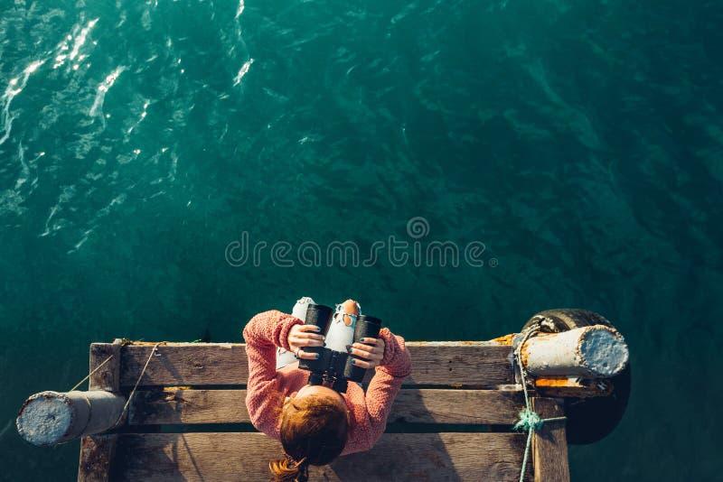 A moça senta-se em Pier And Looks At Sea através dos binóculos, vista superior Conceito do curso da descoberta das férias da aven imagens de stock
