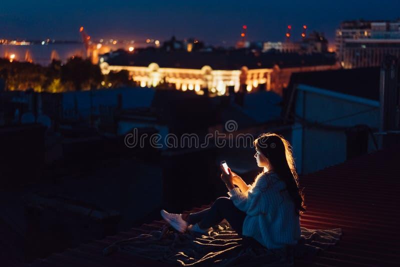 A moça senta-se na noite no telhado de uma casa Noite bonita foto de stock royalty free