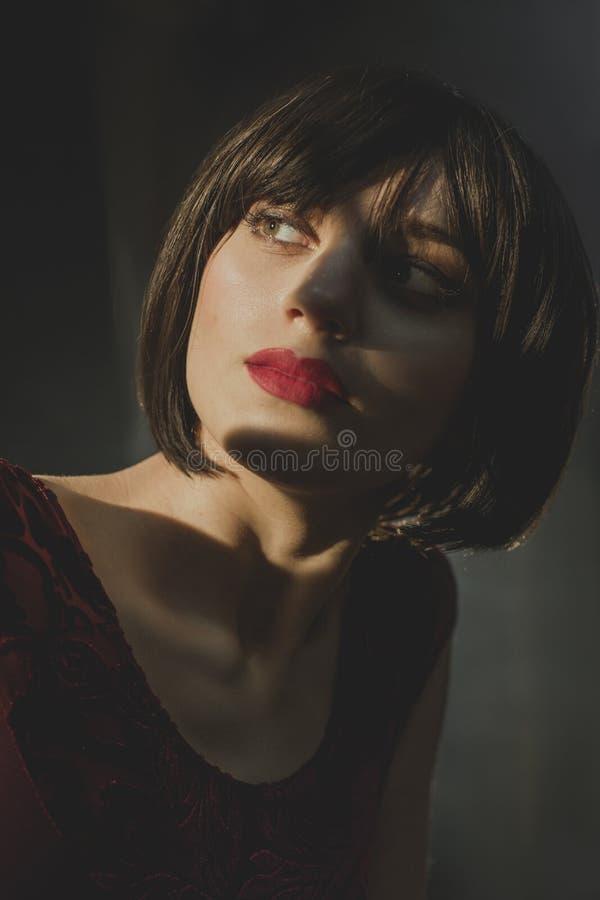 A moça 'sexy' com cabelo escuro olha misteriosamente bordos vermelhos ausentes, bonitos fotos de stock royalty free
