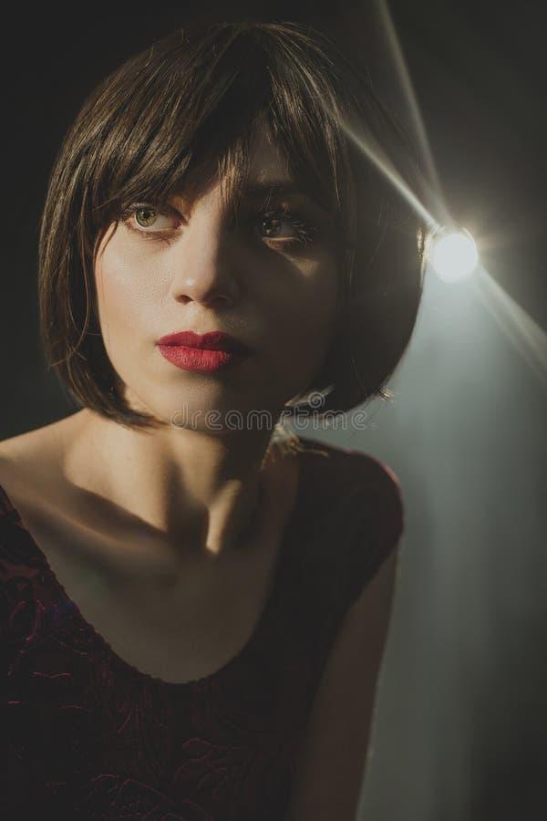 A moça 'sexy' com cabelo escuro olha misteriosamente bordos vermelhos ausentes, bonitos foto de stock royalty free