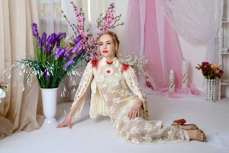 Moça 'sexy' na roupa interior bonita que senta-se no assoalho no estúdio e que olha ao lado fotos de stock royalty free
