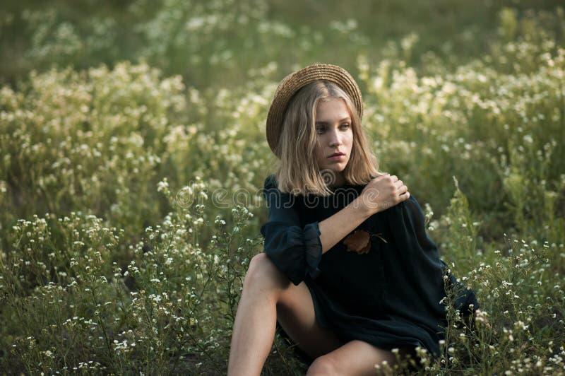 Moça sonhadora em um chapéu de palha e em um vestido preto que sentam-se em um f imagens de stock
