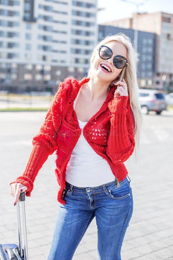 A moça sorri e fala pelo telefone celular suitcase O engodo fotografia de stock royalty free