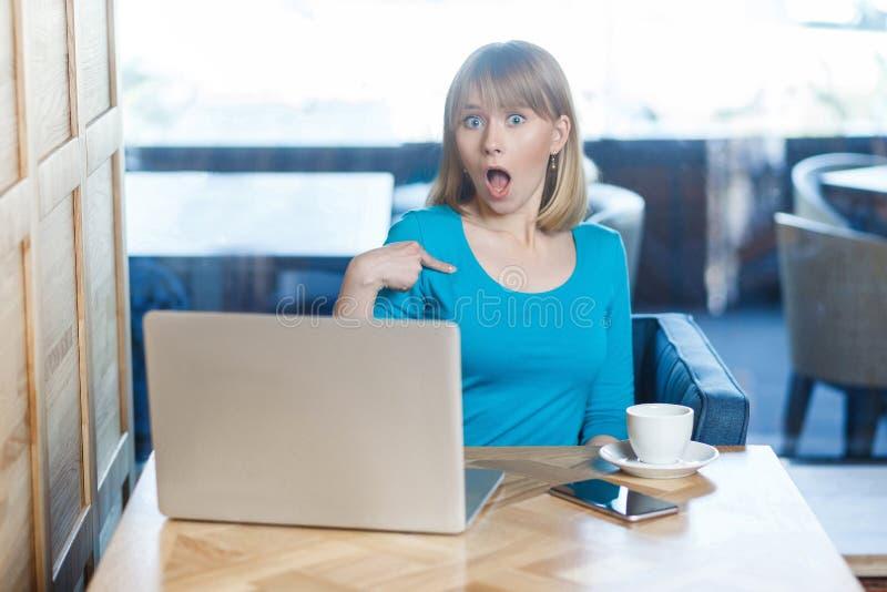 A moça surpreendida com cabelo louro no t-shirt azul está sentando-se apenas no café e está tendo-se a proposta nova para um trab foto de stock royalty free