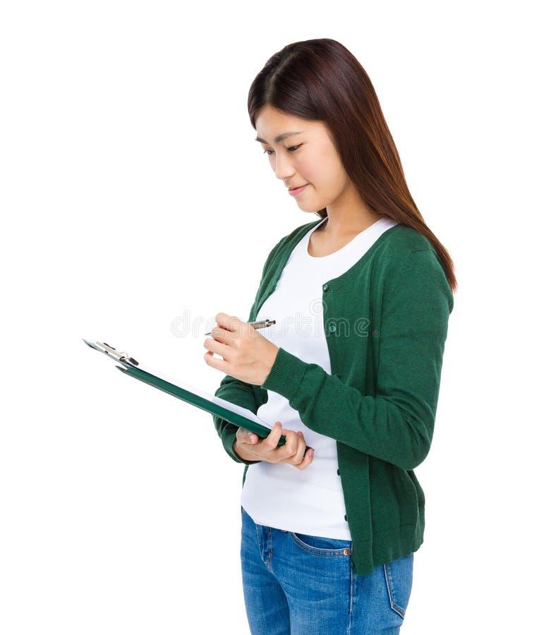 A moça toma a nota na placa da lista de verificação imagens de stock