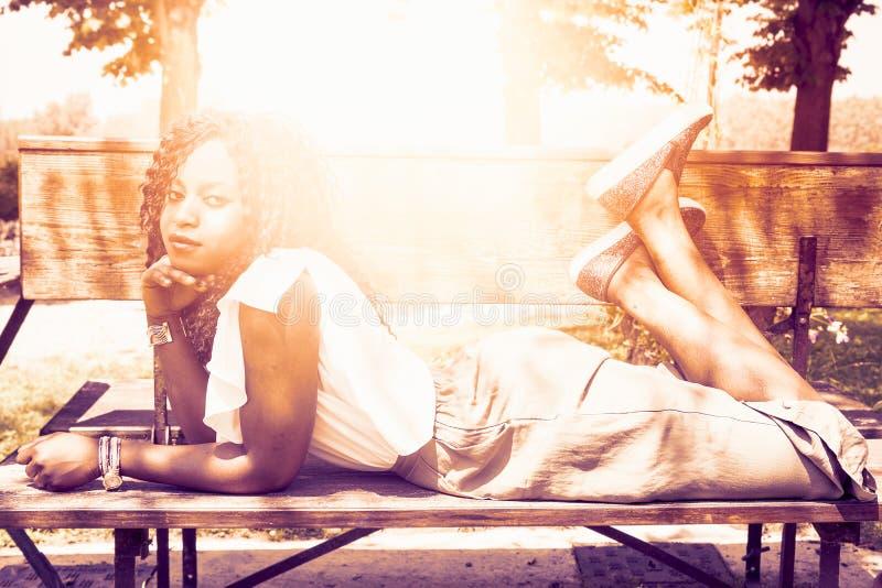 A moça toma pouco para relaxar o encontro em um banco fotografia de stock royalty free