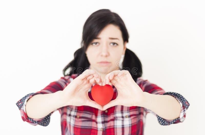 Moça triste que guarda um coração vermelho pequeno e seus dedos sob a forma do coração fotografia de stock royalty free