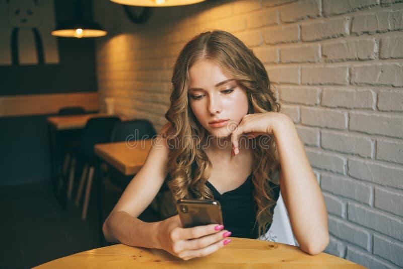 Moça triste que senta-se em um café que parece cansado seu telefone, menina infeliz que olha seu telefone preto, imagens de stock