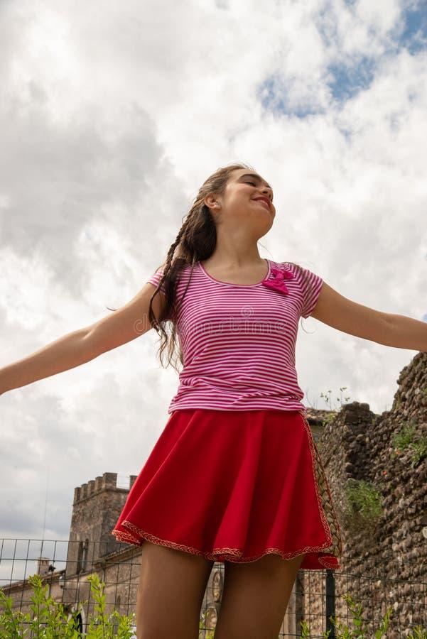 Moça vestida em uma saia vermelha e com o t-shirt listrado vermelho e branco fotos de stock