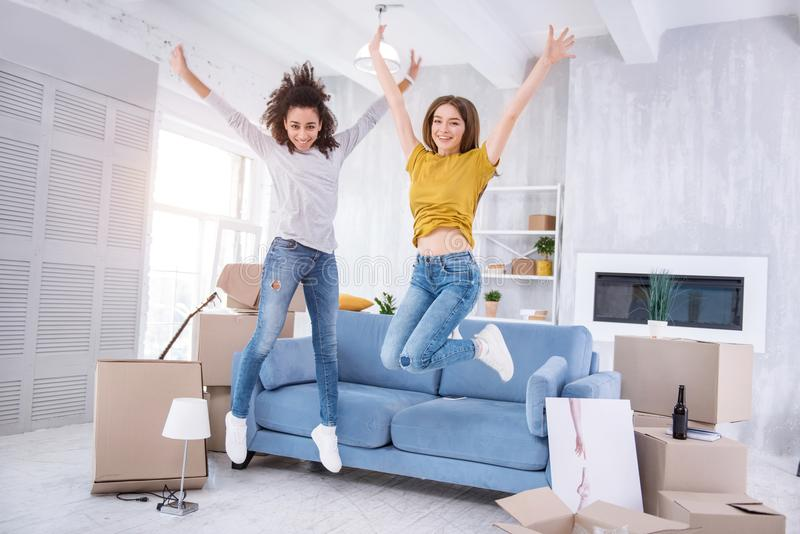 Moças alegres que saltam felizmente no apartamento novo imagem de stock royalty free