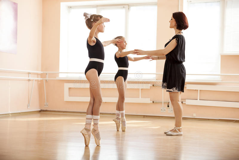 Moças de ajuda do professor do bailado para dançar o pointe do en imagens de stock