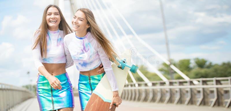 Moças de sorriso com o levantamento do skate exterior fotos de stock