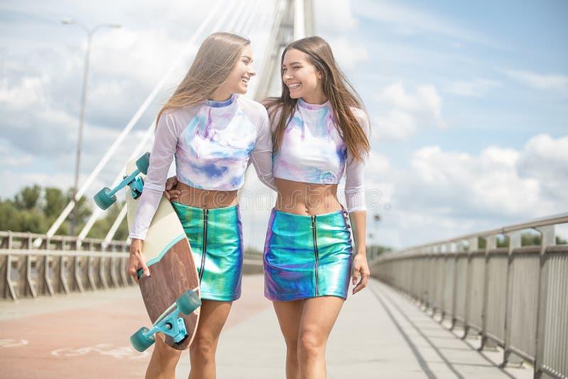 Moças de sorriso com o levantamento do skate exterior imagens de stock royalty free