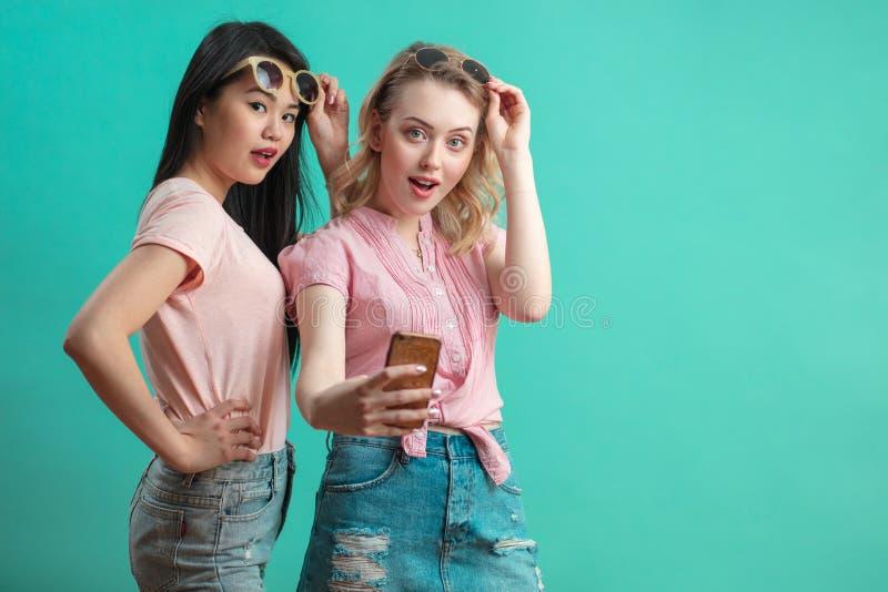 Moças diversas felizes que tomam o selfie com o smartphone contra a parede azul imagem de stock royalty free