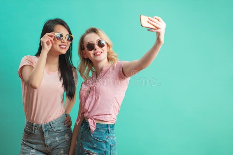 Moças diversas felizes que tomam o selfie com o smartphone contra a parede azul imagens de stock