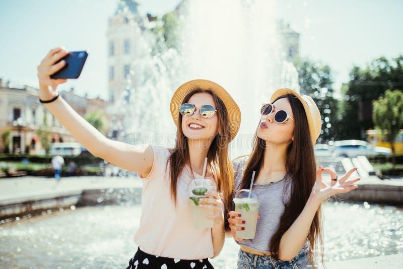 Moças do moderno em melhores amigos dos óculos de sol para beber os cocktail que fazem a foto do auto e que riem na rua da cidade imagens de stock royalty free