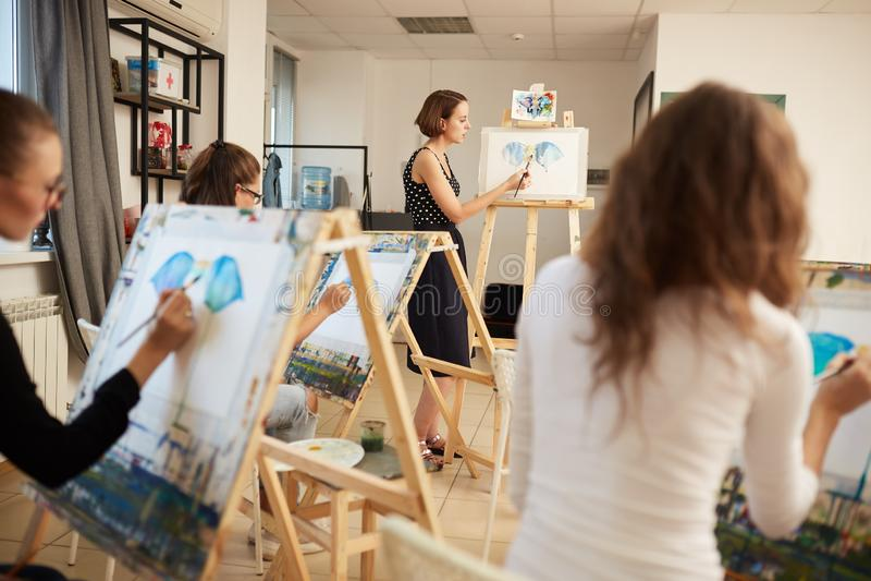 Moças e imagens de tiragem da pintura do professor que sentam-se nas armações no estúdio da arte fotos de stock