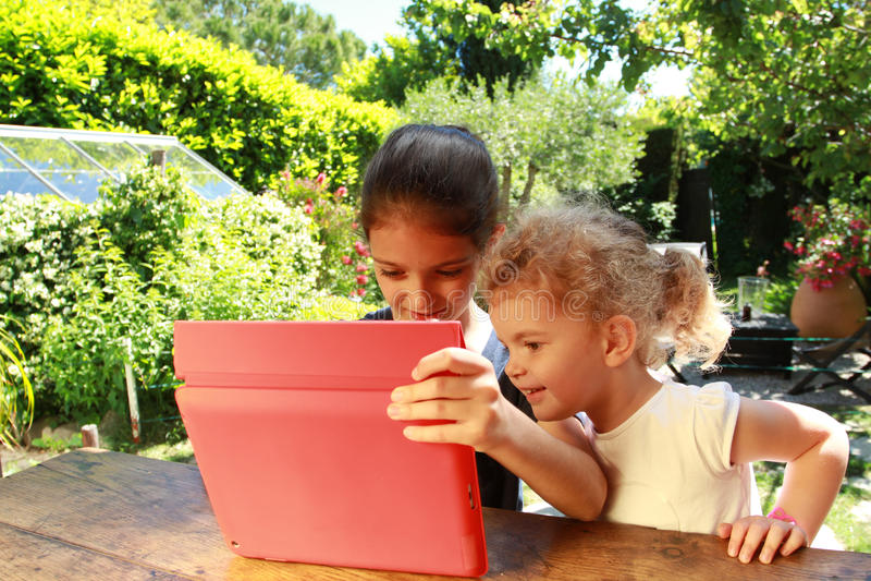 Moças e uma tabuleta do PC foto de stock