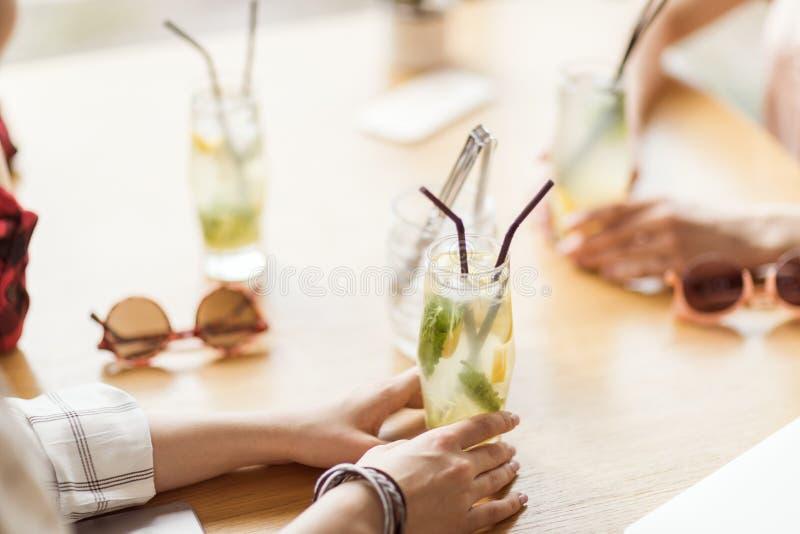 Moças que bebem cocktail junto ao sentar-se na tabela no café foto de stock royalty free