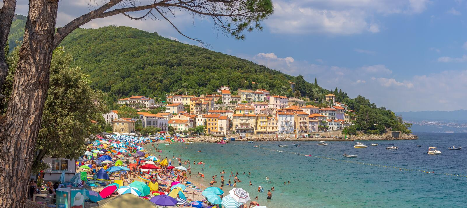 Mošćenička Draga, Croatia - Beautiful Water Colors and Old Town and Coastline at the Adriatic Sea Beach Full of People royalty free stock photography