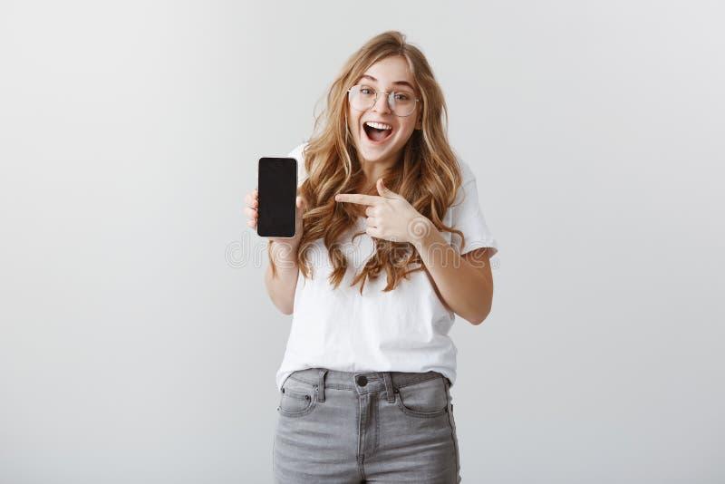 Możesz wyobrażać sobie ty, w końcu kupujący nowy przyrząd Zadowolona z podnieceniem młoda europejska dziewczyna w szkłach, opuszc fotografia stock
