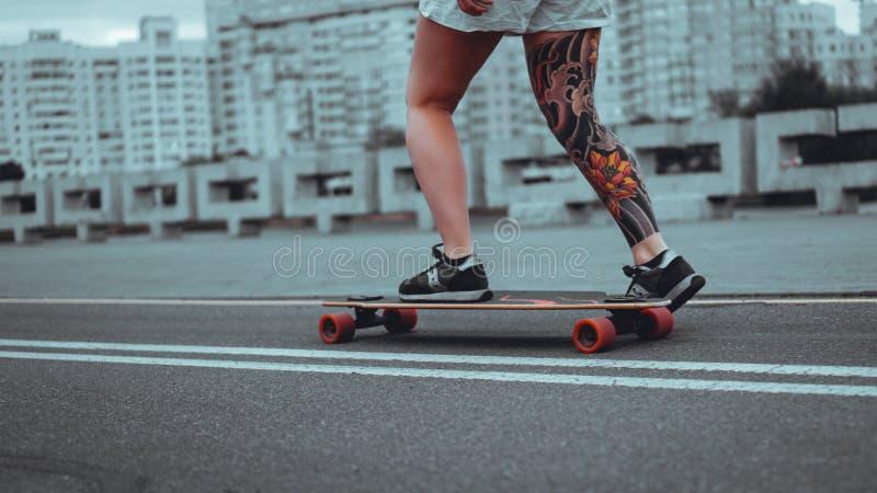 Mo?a bonita com tatuagens com longboard imagem de stock