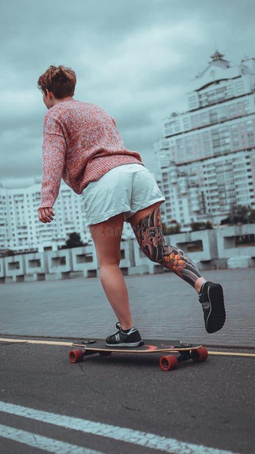 Mo?a bonita com tatuagens com longboard fotografia de stock