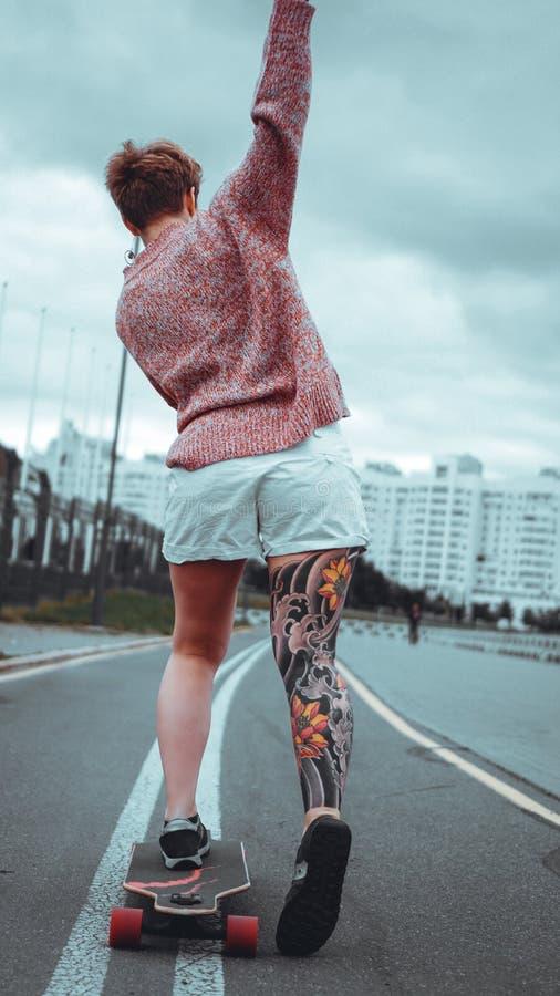 Mo?a bonita com tatuagens com longboard imagens de stock royalty free