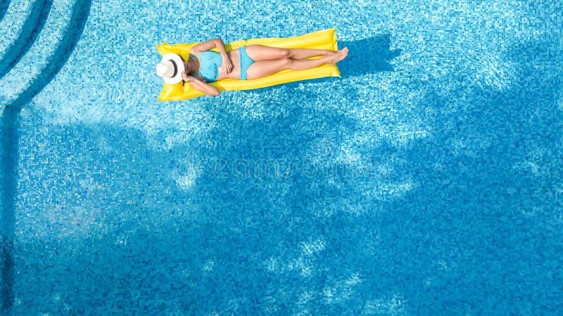 A mo?a bonita que relaxa na piscina, nadadas no colch?o infl?vel e tem o divertimento na ?gua em f?rias em fam?lia fotos de stock royalty free