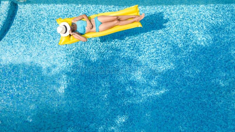 A mo?a bonita que relaxa na piscina, nadadas no colch?o infl?vel e tem o divertimento na ?gua em f?rias em fam?lia fotografia de stock