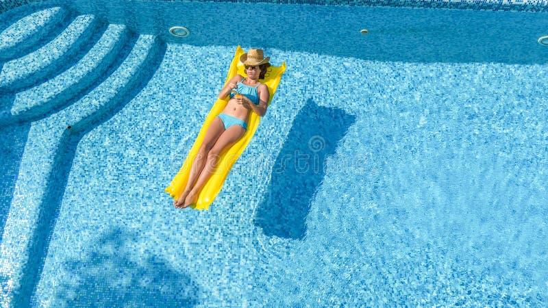 A mo?a bonita que relaxa na piscina, nadadas no colch?o infl?vel e tem o divertimento na ?gua em f?rias em fam?lia fotos de stock