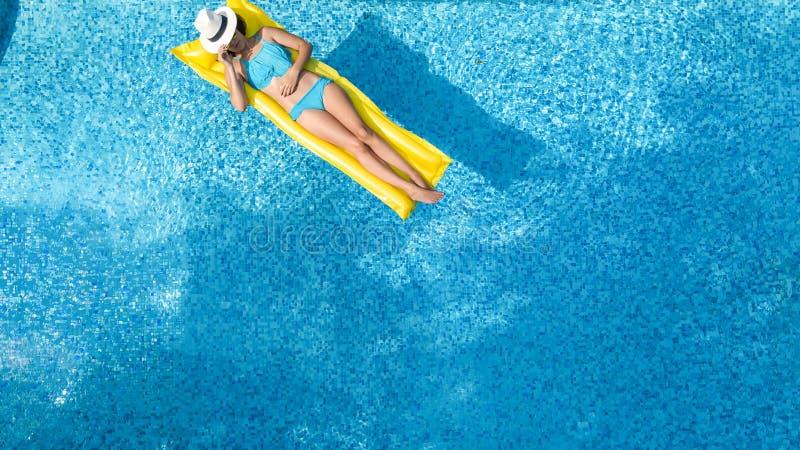 A mo?a bonita que relaxa na piscina, nadadas no colch?o infl?vel e tem o divertimento na ?gua em f?rias em fam?lia foto de stock