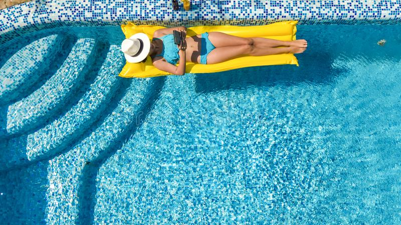 A mo?a bonita que relaxa na piscina, nadadas no colch?o infl?vel e tem o divertimento na ?gua em f?rias em fam?lia foto de stock royalty free