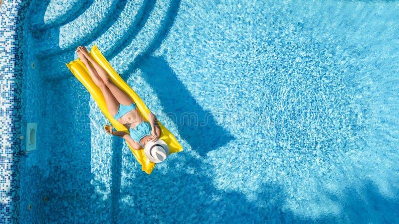 A mo?a bonita que relaxa na piscina, nadadas no colch?o infl?vel e tem o divertimento na ?gua em f?rias em fam?lia fotografia de stock royalty free
