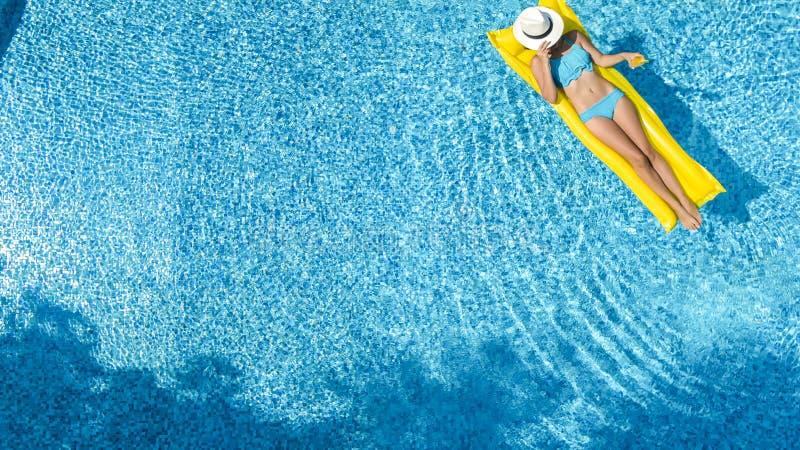 A mo?a bonita que relaxa na piscina, nadadas no colch?o infl?vel e tem o divertimento na ?gua em f?rias em fam?lia imagens de stock royalty free