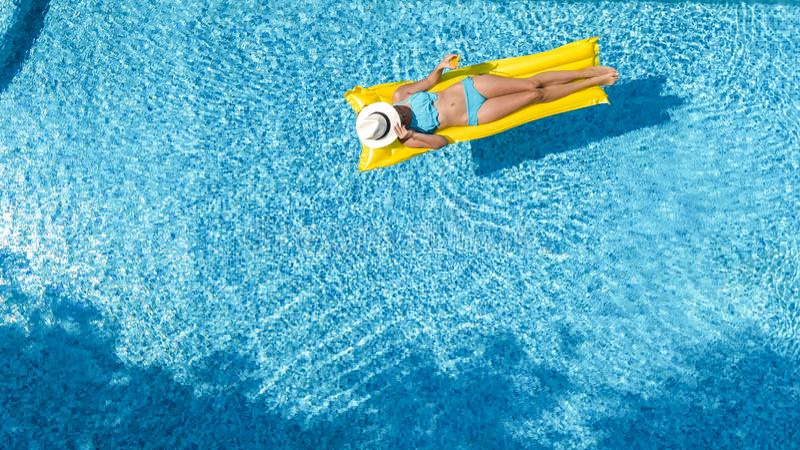 A mo?a bonita que relaxa na piscina, nadadas no colch?o infl?vel e tem o divertimento na ?gua em f?rias em fam?lia imagem de stock royalty free