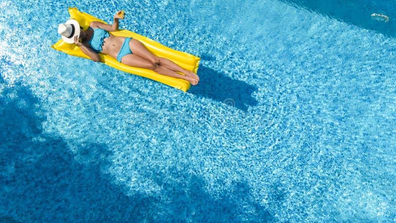 A mo?a bonita que relaxa na piscina, nadadas no colch?o infl?vel e tem o divertimento na ?gua em f?rias em fam?lia imagens de stock