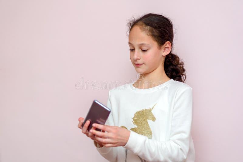 Mo?a bonita que usa o smartpone moderno, mensagem de texto de datilografia do blogger da crian?a do moderno em seu telefone celul fotos de stock