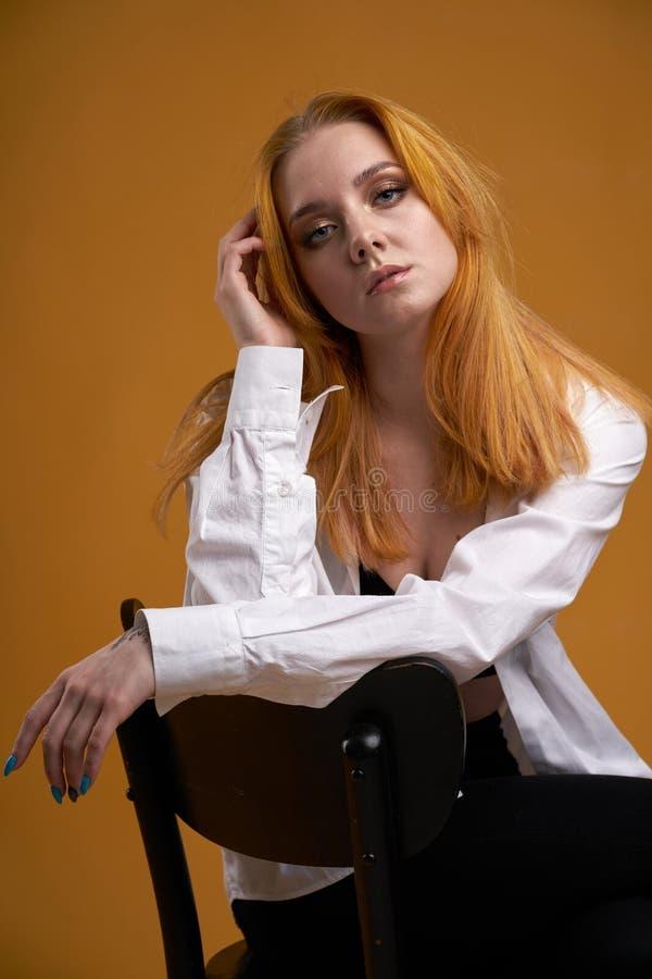 Mo?a ? moda com o cabelo encaracolado, sorrindo cutely, levantando, no fundo amarelo imagem de stock royalty free