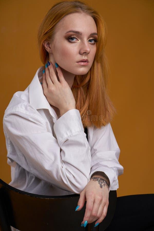Mo?a ? moda com o cabelo encaracolado, sorrindo cutely, levantando, no fundo amarelo fotos de stock royalty free