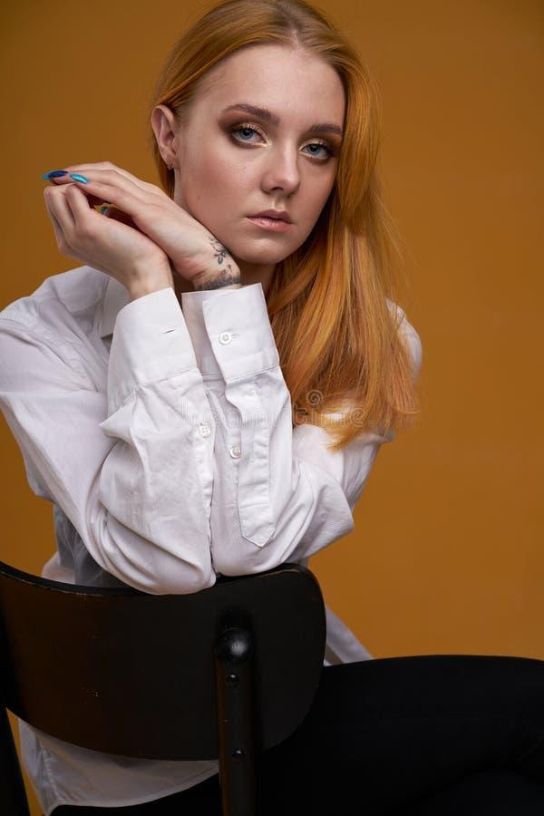 Mo?a ? moda com o cabelo encaracolado, sorrindo cutely, levantando, no fundo amarelo foto de stock