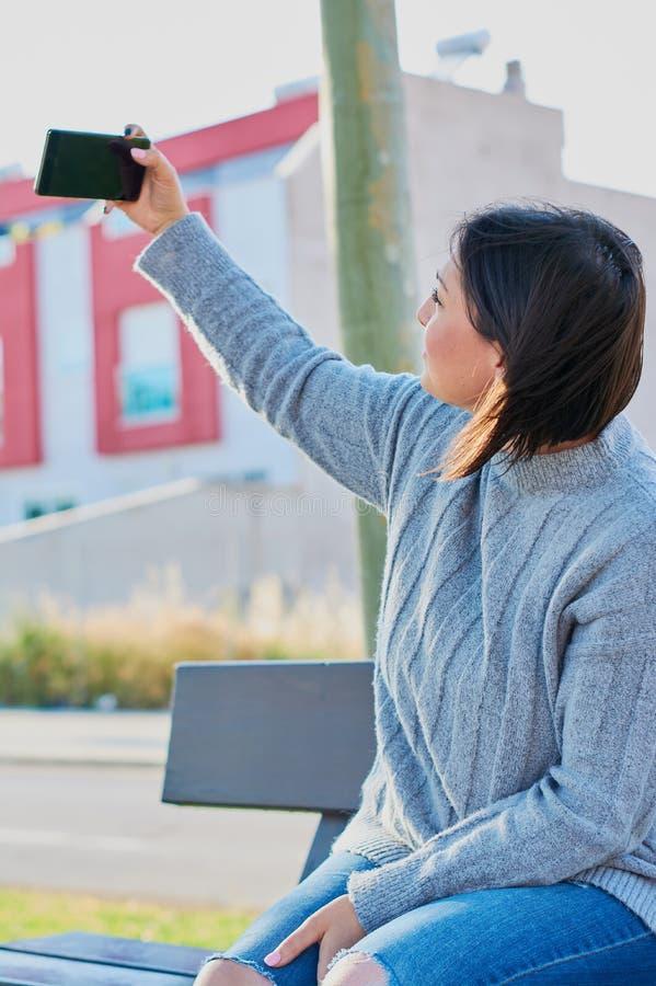 Mo?a que fala no smartphone e em mensagens de datilografia com smartphone imagens de stock royalty free
