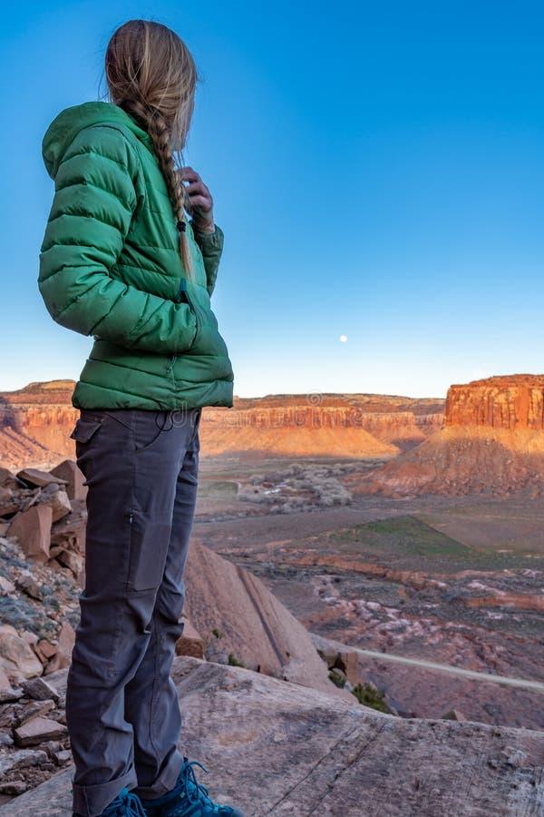 3/21/19 Moab, Utah Kobieta ogląda księżyc wzrost i słońce set, po długiego dnia rockowy pięcie fotografia stock