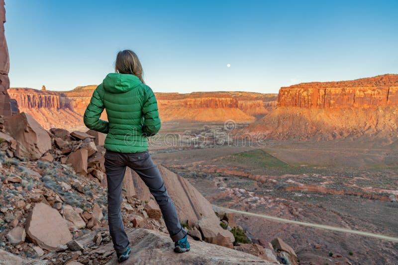 3/21/19 Moab, Utah Mujer que mira la subida de la luna y el sistema del sol, después de un día largo de escalada fotografía de archivo libre de regalías