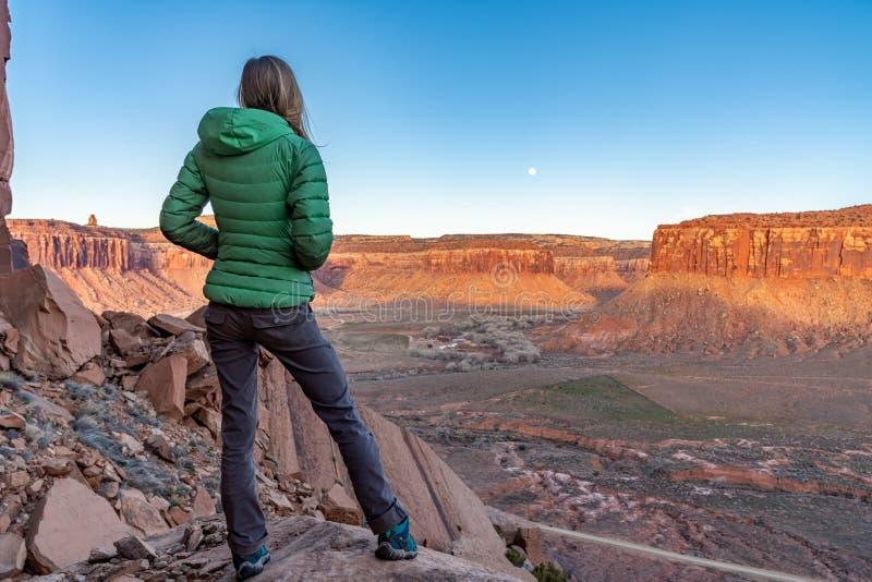 3/21/19 Moab, Utah Mujer que mira la subida de la luna y el sistema del sol, después de un día largo de escalada foto de archivo libre de regalías