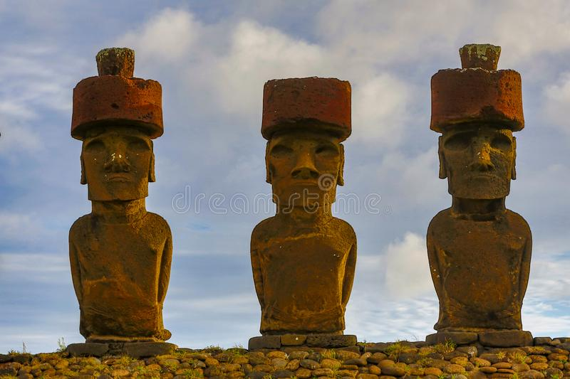 Moai on Easter Island with red topknot hats at Anakena Ahu.  royalty free stock images