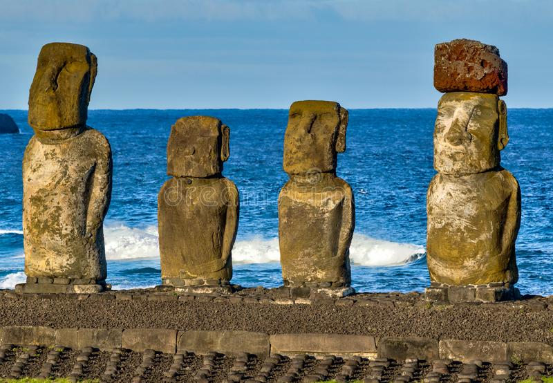 Moai on Easter Island with red topknot hats at Anakena Ahu.  stock image
